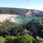 Der Praia Barranco umgeben von grünen Klippen, Algarve, Portugal