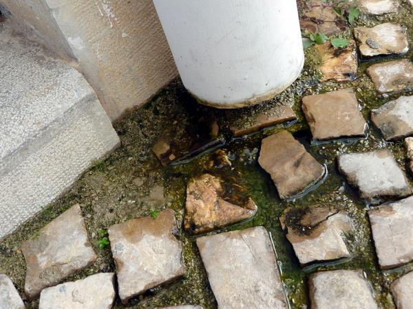 Wasser tropft aus einem Regenrohr auf die Straße