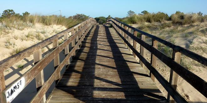 Ein langer Holzsteg führt über die Düne an den Strand von Monte Gordo, Algarve, Portugal