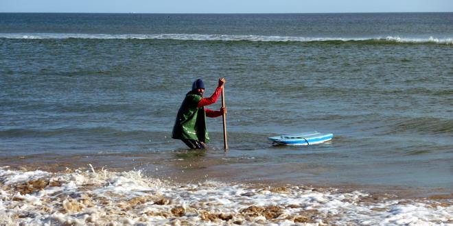 Im Wasser stehen Männer mit langen Stielen in der Hand