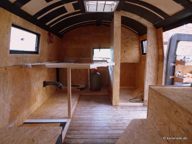 Wohnmobil Selbstausbau Blick vom Wohnzimmer auf Schlafzimmer und Bad und den Durchgang zum Fahrerhaus