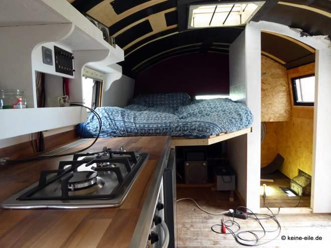 Wohnmobil Selbstausbau Vom Sofa blickt man in die Küche bis ins Schlafzimmer. Der Fußboden ist noch nicht drin, das Bad noch nicht fertig