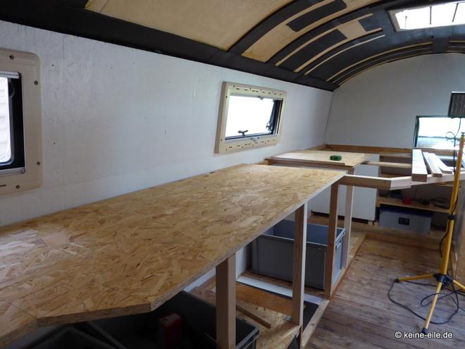 Wohnmobil Selbstausbau Die Arbeitsfläche in der Küche aus OSB-Platte in einer Höhe mit dem Bett